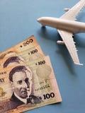 uruguayische Banknoten, weißes Plastikflugzeug und blauer Hintergrund stockbild