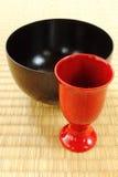 Urushi lacquerware on Tatami mat. Red sake cup and black bowl Royalty Free Stock Image