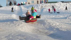 Uryupinsk. Russia - January 21, 2019: Winter vacation: kids riding on inflatable snow tube from a hill. Children climb stock footage