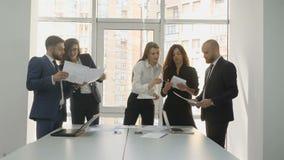 Urzędnicy firmy ` s potomstwa zespalają się, dwa mężczyzna i trzy kobiety dyskutują instalacyjnych dokumenty dla firmy zbiory
