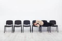 Urzędnik uśpiony na rzędzie krzesła obraz royalty free