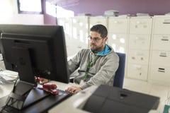 Urzędnik z nastrojowym światłem przy komputerowymi narządzanie kartotekami Zdjęcie Stock