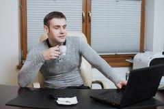 Urzędnika freelancer siedzi przy działaniem na laptopie i biurkiem podczas kawowej przerwy przy biurem Fotografia Royalty Free