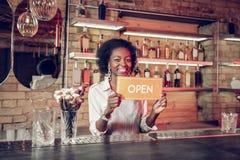 Urzekający promieniejący dorosłego amerykanina barmanu mienie otwarty podpisuje wewnątrz ręki fotografia stock