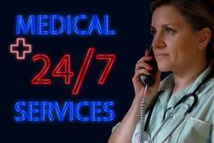 Usługi zdrowotne 24 7 pojęciem Neonowy rozjarzony signboard i doktorskie kobiety z telefonem i stetoskopem odpowiadamy telefon w  zdjęcia royalty free