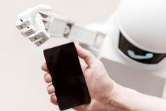 Usługowy robot dosięga smartphone zdjęcie royalty free