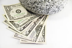 US 1,5,50 dollar bill and a rock. American 1,5,50 dollars bills held down by a round granite rock stock image