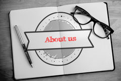 About us against overhead of open notebook with pen and glasses Royalty Free Stock Images