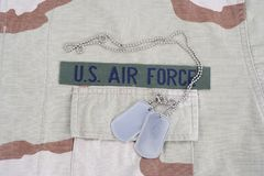 US AIR FORCE branch tape with dog tags on desert camouflage uniform. Background Stock Photos