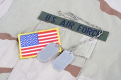 US AIR FORCE branch tape with dog tags and flag patch on desert camouflage uniform. Background Stock Images