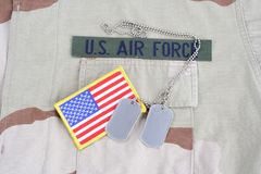 US AIR FORCE branch tape with dog tags and flag patch on desert camouflage uniform. Background Royalty Free Stock Images