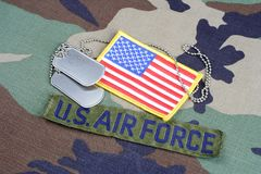 US AIR FORCE branch tape, flag patch and dog tags on woodland camouflage uniform. Background Royalty Free Stock Image