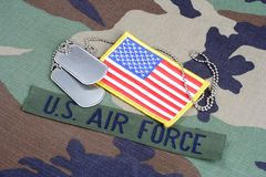 US AIR FORCE branch tape, flag patch and dog tags on woodland camouflage uniform. Background Stock Image