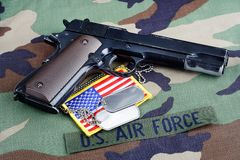 US AIR FORCE branch tape , M1911 handgun with dog tags on woodland camouflage uniform. Background Stock Images
