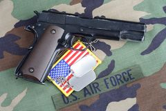 US AIR FORCE branch tape , M1911 handgun with dog tags on woodland camouflage uniform. Background Stock Photography