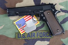 US AIR FORCE branch tape , M1911 handgun with dog tags on woodland camouflage uniform. Background Royalty Free Stock Photo