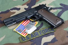 US AIR FORCE branch tape , M1911 handgun with dog tags on woodland camouflage uniform. Background Stock Photos