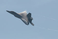 US Air Force F22 Raptor. With water vapor on wings and vapor trails Stock Photos