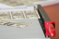 Us american dollar money bills printed in a sheet of paper in a paper cutter. Manufacture work Royalty Free Stock Photography