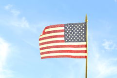 Us or American flag waving in blue sky background Stock Images