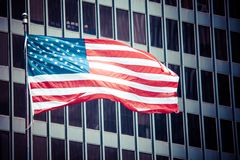 US american symbol flag over blue modern city buildings Royalty Free Stock Image