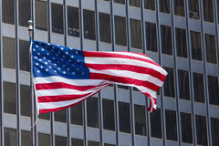 US american symbol flag over blue modern city buildings Stock Photos