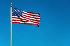 Us-amerikanska flaggan som vågr i wind med den blåa skyen Royaltyfria Bilder