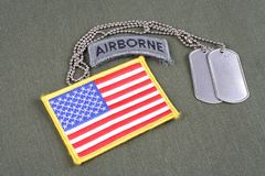 US ARMY airborne tab with dog tag and flag patch on olive green uniform. Background Royalty Free Stock Photo