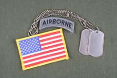 US ARMY airborne tab with dog tag and flag patch on olive green uniform. Background Stock Photo