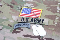 US ARMY airborne tab, flag patch, with dog tag on camouflage uniform. Background Royalty Free Stock Image