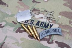 US ARMY airborne tab, flag patch, with dog tag and 5.56 mm rounds on camouflage uniform. US ARMY airborne tab, flag patch,  with dog tag and 5.56 mm rounds on Stock Photos