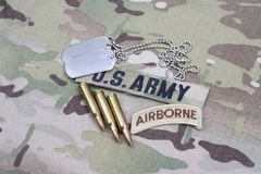 US ARMY airborne tab, flag patch, with dog tag and 5.56 mm rounds on uniform. US ARMY airborne tab, flag patch, with dog tag and 5.56 mm rounds on camouflage Royalty Free Stock Photo