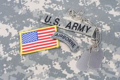 US ARMY airborne tab, flag patch,  with dog tags on camouflage uniform. Background Stock Image