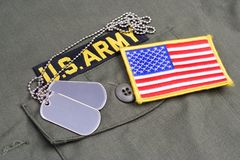 US ARMY Branch Of Service Tape with dog tags and flag patch on olive green uniform. Background Stock Photography