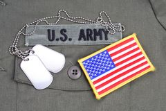 US ARMY Branch Of Service Tape with dog tags and flag patch on olive green uniform. Background Royalty Free Stock Photos