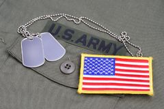 US ARMY Branch Of Service Tape with dog tags and flag patch on olive green uniform. Background Stock Image