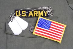US ARMY Branch Of Service Tape with dog tags and flag patch on olive green uniform. Background Stock Photos