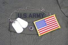 US ARMY Branch Of Service Tape with dog tags and flag patch on olive green uniform. Background Royalty Free Stock Images