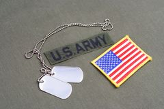 US ARMY Branch Of Service Tape with dog tags and flag patch on olive green uniform. Background Royalty Free Stock Image