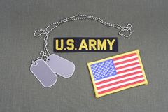 US ARMY Branch Of Service Tape with dog tags and flag patch on olive green uniform. Background Royalty Free Stock Photography