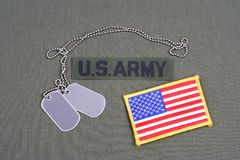 US ARMY Branch Of Service Tape with dog tags and flag patch on olive green uniform. Background Stock Photo
