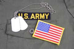 US ARMY Branch Of Service Tape with dog tags and flag patch on olive green uniform. Background Royalty Free Stock Photo