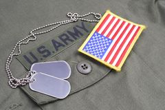 US ARMY Branch Of Service Tape with dog tags and flag patch on olive green uniform. Background Stock Images
