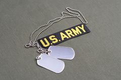 US ARMY Branch Of Service Tape with dog tags on olive green uniform. Background Royalty Free Stock Photo