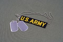 US ARMY Branch Of Service Tape with dog tags on olive green uniform. Background Stock Images