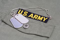 US ARMY Branch Of Service Tape with dog tags on olive green uniform. Background Stock Image