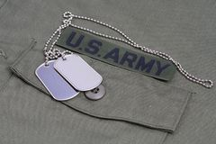 US ARMY Branch Of Service Tape with dog tags on olive green uniform. Background Royalty Free Stock Image