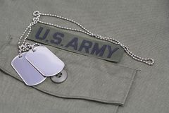 US ARMY Branch Of Service Tape with dog tags on olive green uniform. Background Royalty Free Stock Photos