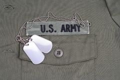 US ARMY Branch Of Service Tape with dog tags on olive green uniform. Background Stock Photo
