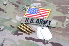 US ARMY branch tape with dog tag flag patch and 5.56 mm rounds on camouflage uniform. Background royalty free stock image